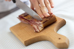 Chef cutting bacon into strips Stock Photography