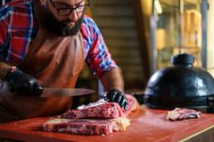 Chef cutting beef steakes in a restaurant
