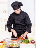 Chef cutting bell peppers in kitchen Royalty Free Stock Photography