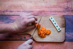 Chef is cutting carrot on a wooden cutting board with sharp knif. E and word for bosnian, serbian, croatian chef written with box letters Stock Photography