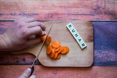 Chef is cutting carrot on a wooden cutting board with sharp knif. E and word for bosnian, serbian, croatian chef written with box letters Royalty Free Stock Photo