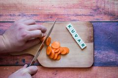 Chef is cutting carrot on a wooden cutting board with sharp knif. E and word for bosnian, serbian, croatian chef written with box letters Royalty Free Stock Images