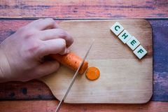 Chef is cutting carrot on a wooden cutting board with sharp knif. E and word chef written with box letters Royalty Free Stock Photography