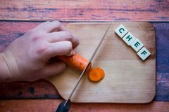 Chef is cutting carrot on a wooden cutting board with sharp knif. E and word chef written with box letters Stock Image
