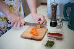 Chef is cutting carrot on a wooden cutting board with sharp knif. E Royalty Free Stock Photography