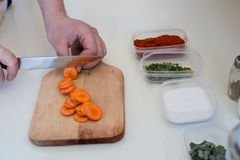 Chef is cutting carrot on a wooden cutting board with sharp knif. E Royalty Free Stock Image