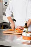 Chef Cutting Carrots At Kitchen Counter Royalty Free Stock Images
