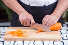 Chef is cutting carrots Royalty Free Stock Images
