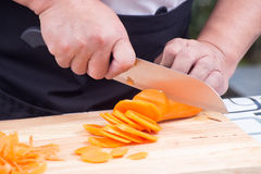 Chef is cutting carrots Stock Images