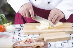 Chef cutting cheese with knife before cooking Stock Photography