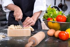 Chef Cutting cook Homemade makes dough fresh Pasta. Royalty Free Stock Images