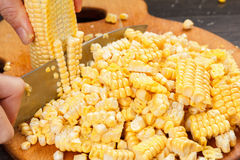 Chef cutting corn for cooking. Stock up on winter food. Royalty Free Stock Images