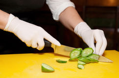 Chef is cutting cucumber. Female chef is cutting cucumber on yellow plank Royalty Free Stock Image