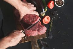 Chef cutting filet mignon on wooden board. Man slicing filet mignon on wooden board at restaurant kitchen. Chef preparing fresh meat for cooking. Modern cuisine royalty free stock images