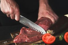 Chef cutting filet mignon on wooden board. Man slicing filet mignon on wooden board at restaurant kitchen. Chef preparing fresh meat for cooking. Modern cuisine stock photo