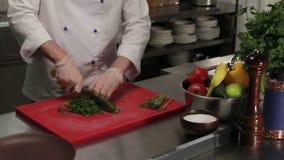 Chef cutting fresh greenery, medium shot. Chef cutting fresh greenery finely, dill and parsley, medium shot stock video