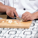 Chef is cutting garlic / Stock Images
