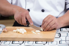 Chef is cutting garlic Royalty Free Stock Photo