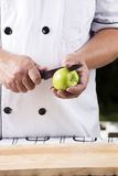 Chef cutting green apple Royalty Free Stock Images