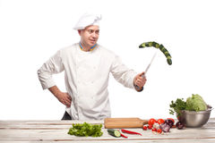 Chef cutting a green cucumber in his kitchen Stock Photos