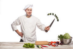 Chef cutting a green cucumber in his kitchen Stock Images