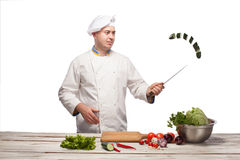 Chef cutting a green cucumber in his kitchen Royalty Free Stock Image