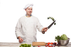 Chef cutting a green cucumber in his kitchen Royalty Free Stock Photography