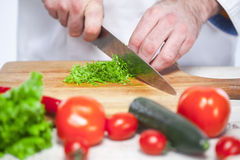 Chef cutting a green lettuce his kitchen Stock Images