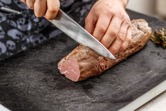 Chef is cutting meat Royalty Free Stock Photo