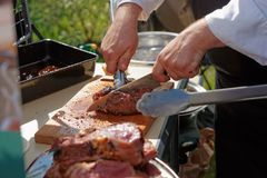 Chef is cutting meat. At outdoor kitchen Stock Photos