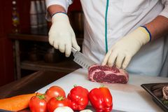 Chef cutting meat. On steaks with knife Royalty Free Stock Photography