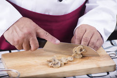 Chef cutting mushroom with knife before cooking Royalty Free Stock Images