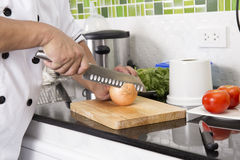 Chef cutting onion for making Hamburger Stock Images