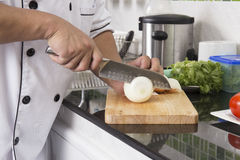 Chef cutting onion for making Hamburger Stock Image
