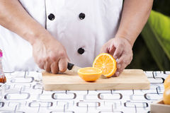 Chef cutting orange Royalty Free Stock Photography