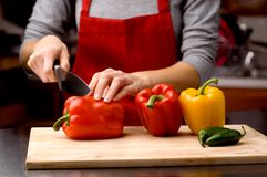 Chef cutting peppers Royalty Free Stock Photography