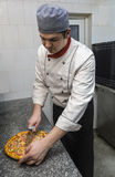 Chef Cutting the Pizza. Chef cutting a pizza in a restaurant kitchen Royalty Free Stock Images