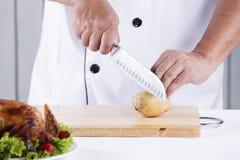 Chef cutting potato Royalty Free Stock Photos