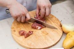 Chef Cutting Raw Meat auf dem hölzernen Block Lizenzfreie Stockfotos