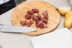 Chef Cutting Raw Meat auf dem hölzernen Block Stockfoto