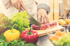 Chef cutting raw meat on wooden board Royalty Free Stock Photo