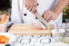 Chef cutting raw pork on wooden board Stock Photo