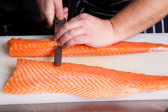 Chef cutting salmon fish. On fillets with knife Stock Photo