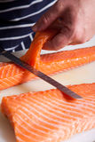 Chef cutting salmon fish. On fillets with knife Royalty Free Stock Photography