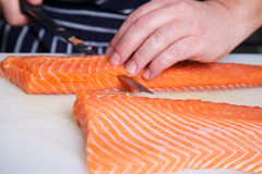 Chef cutting salmon fish. On fillets with knife Stock Image