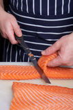 Chef cutting salmon fish. On fillets with knife Royalty Free Stock Photo