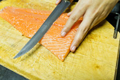 Chef cutting salmon fish. On fillets with knife Stock Photography