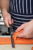 Chef cutting salmon fish on fillets. With knife Stock Image