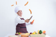Chef cutting sausage in the air Stock Image