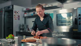 Chef cutting sausages on the cutting board. Chef cutting sausages, frankfurters on the cutting board stock footage